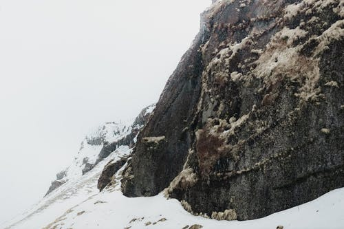 Rough boulder of remote mountain covered with white snow in misty cold valley