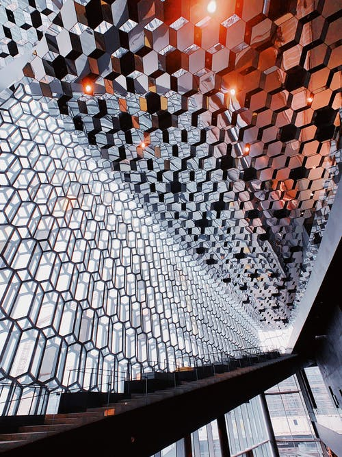 From below of modern geometric ceiling with cell metal ornament in spacious hallway