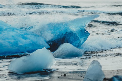 Crystal ice chunks on remote empty shoreline with cold foam waves running on ground