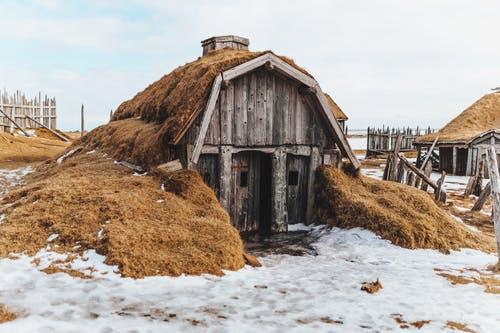 Shabby wooden house with grass covered roof in snowy terrain with forgotten village