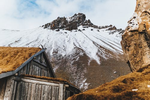 Low angle of aged wooden house at bottom of rocky mountain ridge with snow on slope