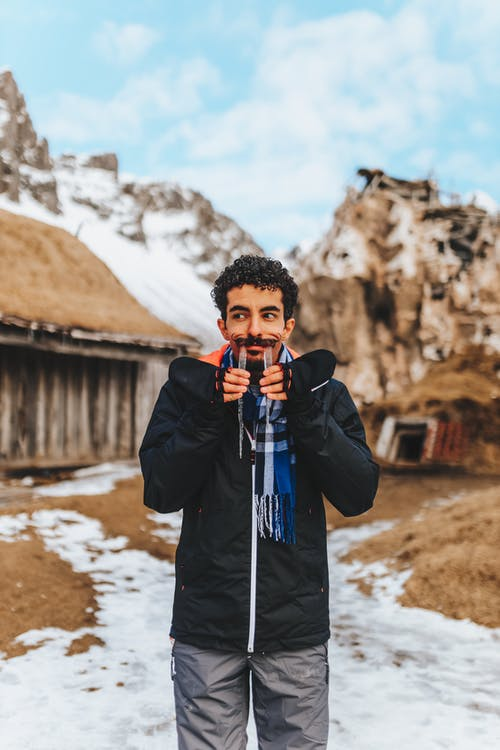 Funny ethnic male in warm jacket making grimace with icicle tusks in mouth looking away against cold nature