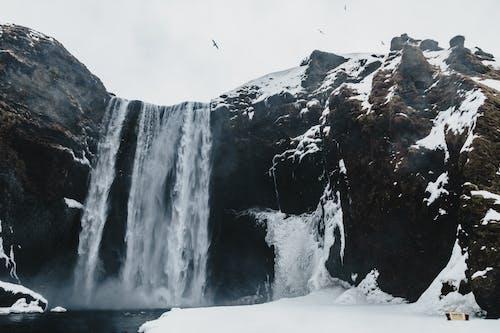 Scenery view of rapid cascade with foamy water flow in rough mounts near pond in winter