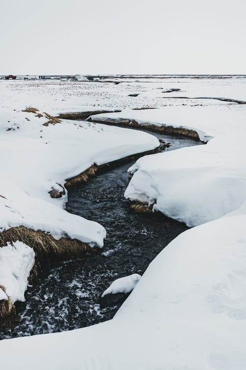Narrow river between snowy terrain under sky