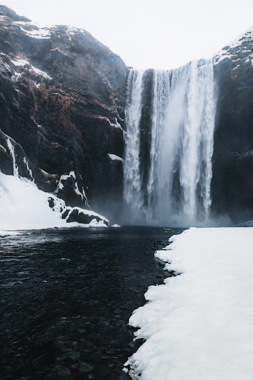 Waterfall near river in mounts with snowy terrain