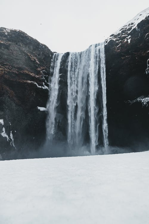Scenery view of fast foamy waterfall in bristly mounts near snowy surface under sky