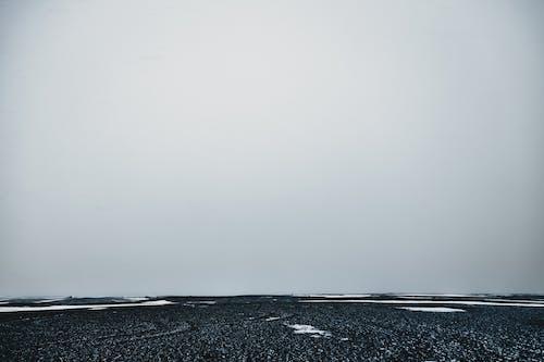 Dry snowy terrain under white sky in fog