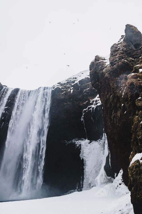 From below of fast waterfall in rough mounts near snowy terrain under white sky with flying birds