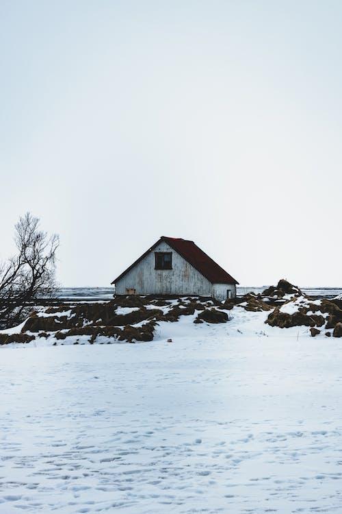 Old house on snowy terrain near sea under sky
