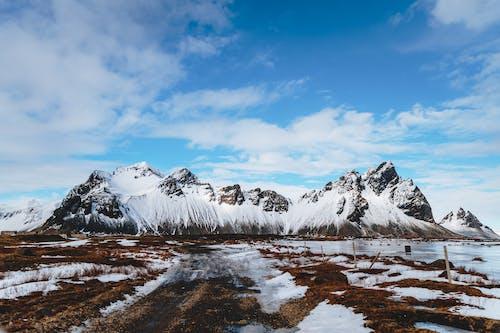 Rocks near sea and snowy terrain under sky