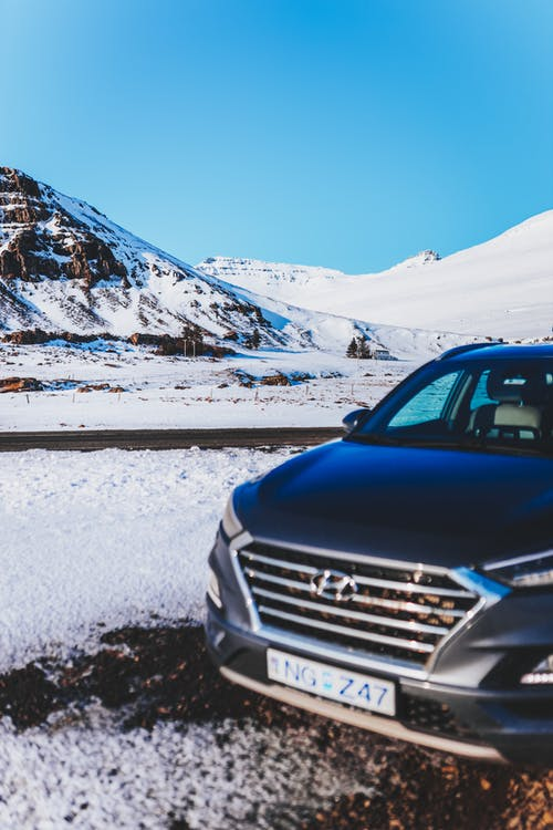 Contemporary automobile parked near snowy mounts under bright sky in winter in daylight