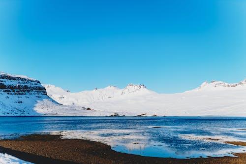 Snowy mounts near ocean under blue sky