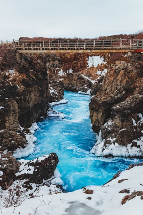 From above of colorful narrow river flow between bristly snowy rocks under aged bridge in winter