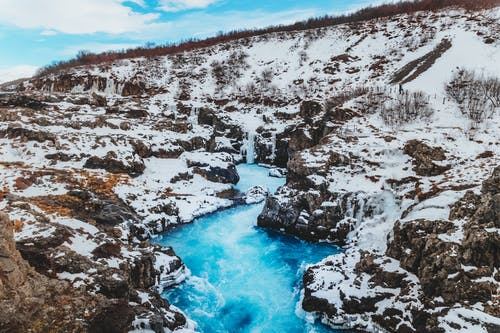 From above scenery view of blue wavy river fluid between rough snowy mounts with dry grass under sky in winter