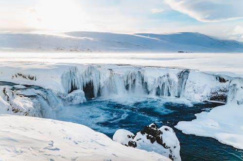 Foamy cascades near pond and snowy mountains under bright sky