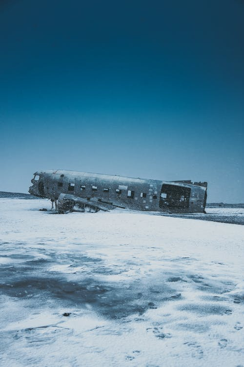 Old ruined aircraft after disaster on snowy terrain under blue sky in winter