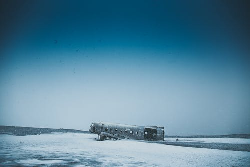 Old airplane after disaster on snowy land near mounts