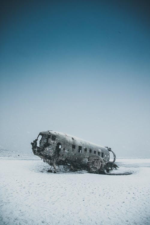 Ruined airplane after disaster on snowy terrain under sky in winter in daytime