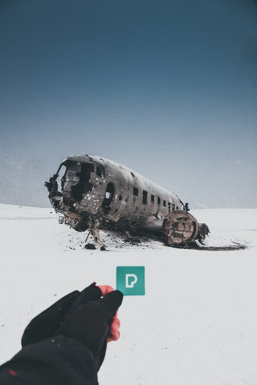 Crop unrecognizable person demonstrating small sticker with letter P against ruined plane after accident on snowy land under sky