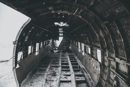 Aged rusty aircraft interior on snowy terrain after disaster