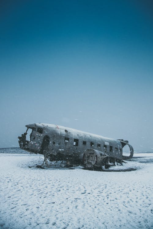 Crashed aircraft after disaster on snowy land under sky