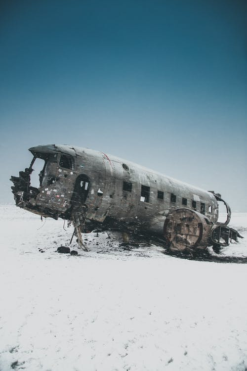 Black and White Airplane on Snow Covered Ground