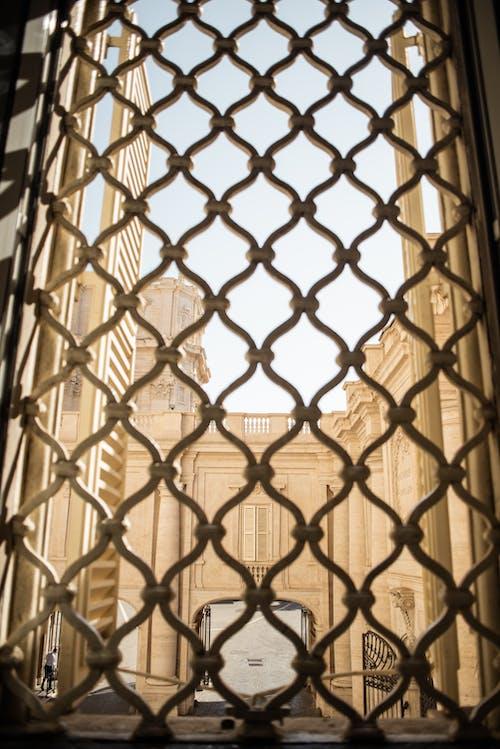 Decorative lattice window overlooking inner yard of cream colored building on sunny day