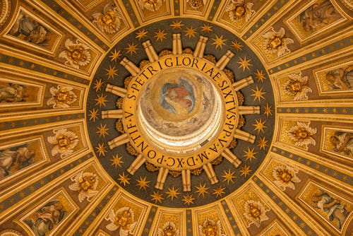 From below wonderful ornamental design of ancient dome inside St. Peters Basilica in Rome