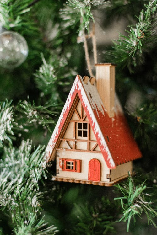 Cute wooden toy house hanging on decorated artificial Christmas tree during festive season in December