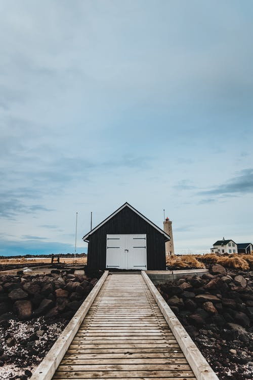 Brown Wooden House on Brown Rocky Shore Under Gray Sky