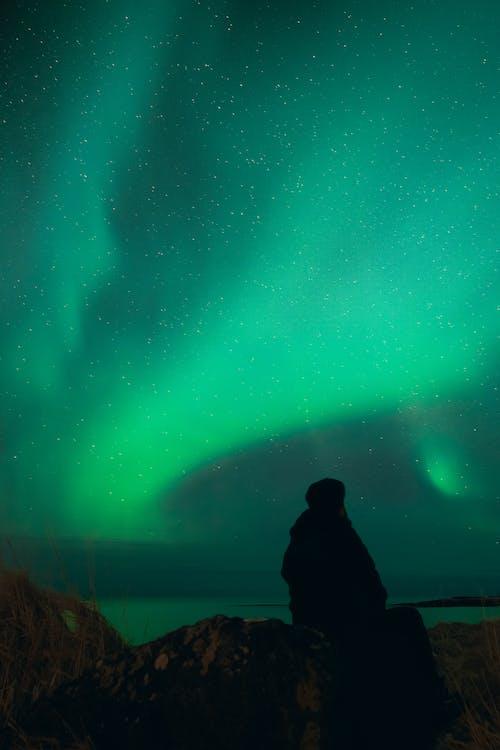 Silhouette of unrecognizable traveler admiring sea in polar night