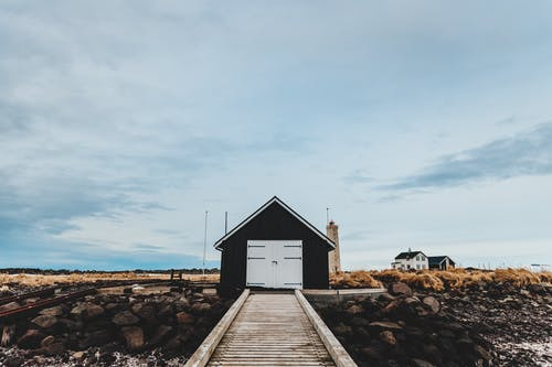 Black and White Wooden House on Brown Rocky Shore Under White Cloudy Sky