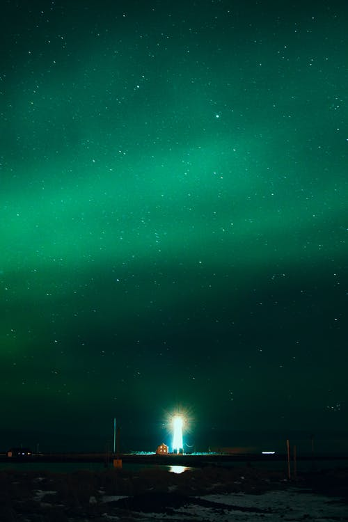 Beacon with glowing rays under colorful green sky with northern lights at dusk