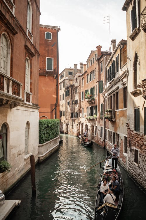 Gondolas floating on narrow canal in Venice