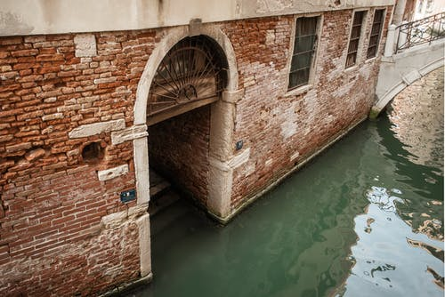 Waterway near old brick building with arch
