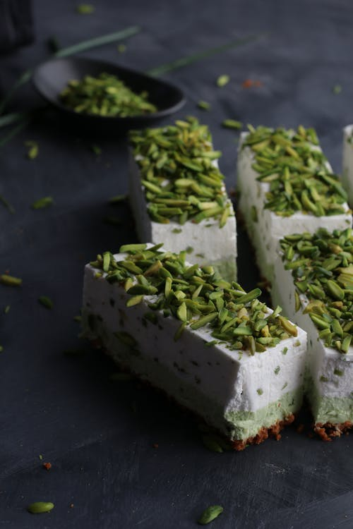 From above of similar delicious cake pieces with tender texture decorated with bright crunchy pistachios