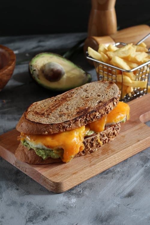 From above of yummy sandwich with crispy bread loafs and bright cheddar cheese near avocado and French fries