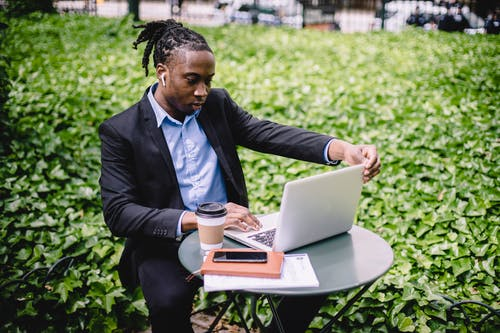 Concentrated ethnic businessman using laptop in park