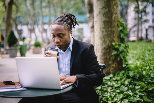 Thoughtful black businessman using laptop in park