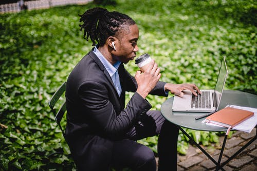 Side view contemplative black businessman in formal outfit surfing modern netbook while enjoying hot drink and listening to music via earbuds in sunny park
