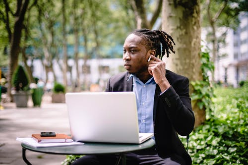 Pensive black businessman with earbuds and laptop in park