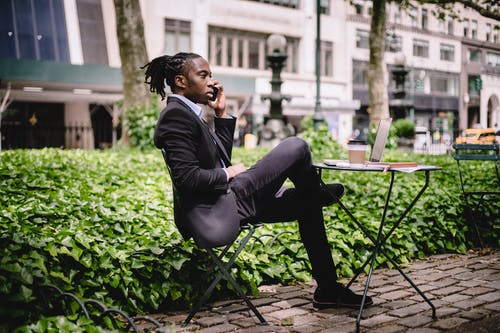 Side view serious African American businessman in black formal wear sitting at table in city park with legs crossed and having conversation via modern smartphone