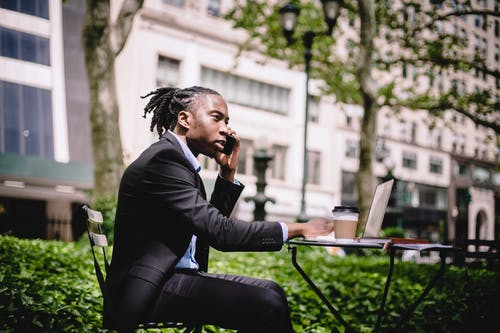 Thoughtful black businessman with laptop talking on smartphone in garden