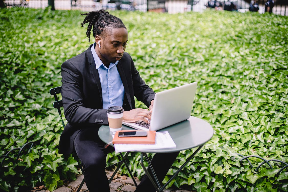 Concentrated African American businesswoman in earbuds wearing formal black suit sitting at table in city garden and typing on netbook