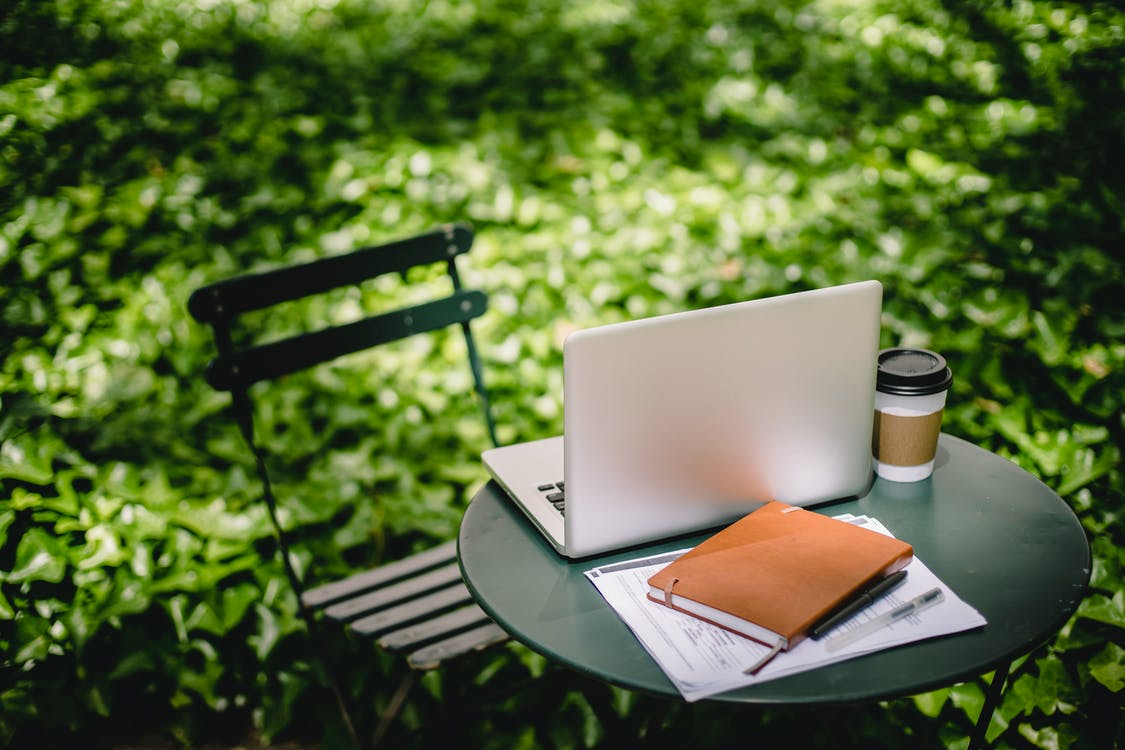 Cozy table with laptop and notebook in park