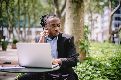 Concentrated black businessman in formal black outfit sitting at table in summer park while listening to audio via earbuds and working remotely on netbook