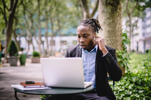 Concentrated young black male with dreadlocks in formal wear having video conversation on laptop using TWS earphones while sitting in outdoor cafe