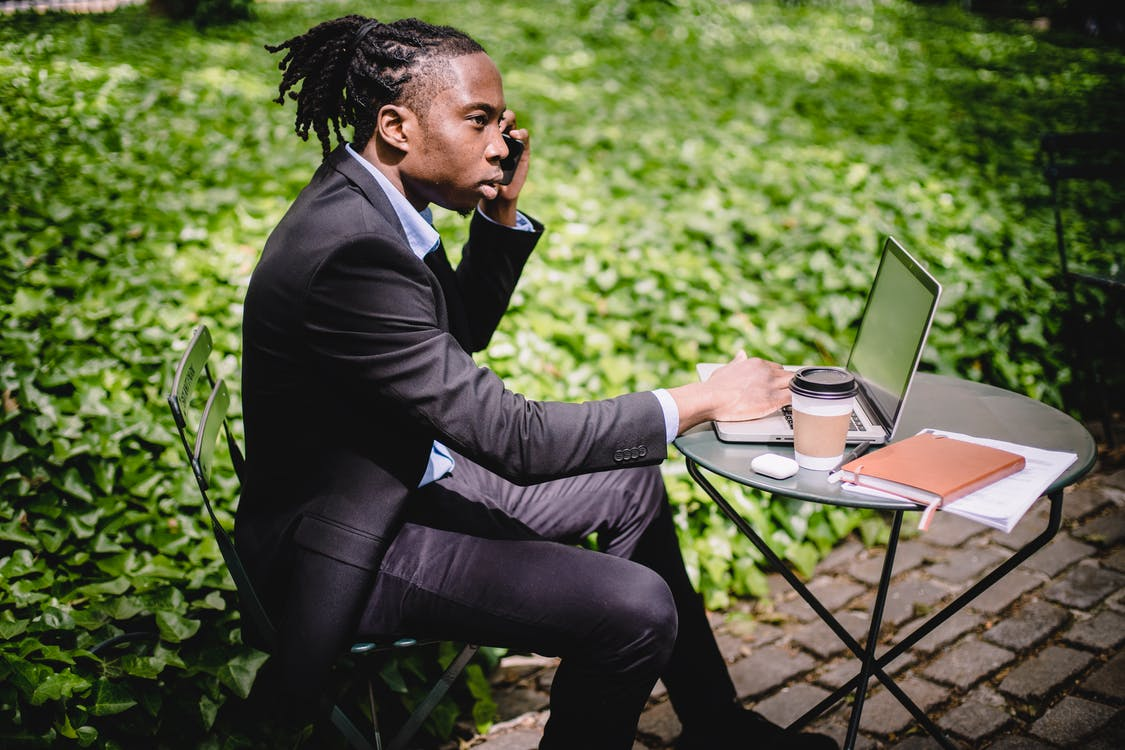 Serious African American male talking on smartphone while working on laptop in summer cafe