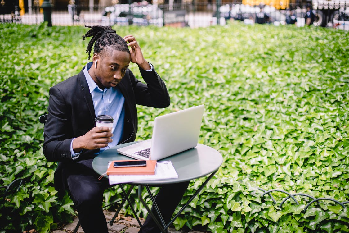 Focused young African American male freelancer with dreadlocks in formal wear drinking coffee in street cafe and scratching head while reading report on laptop