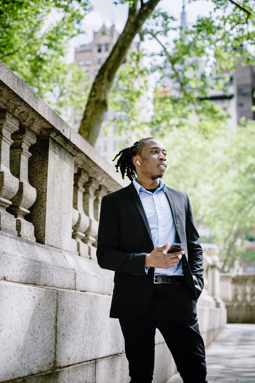 Stylish young black man with smartphone standing on sidewalk in downtown